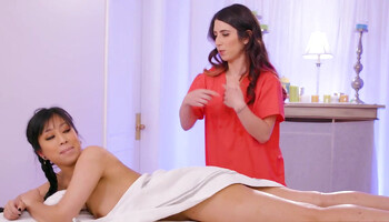 Horny masseuse touches brunette's private parts during session