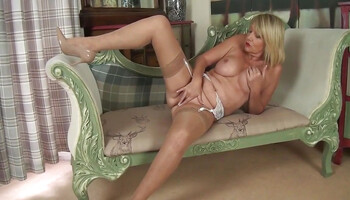 Horny mature blonde is stripping and masturbating for the camera